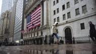 Ein Fußgänger mit einem Mundschutz vor der New Yorker Stock Exchange: Die Märkte in Amerika und weltweit stehen vor einer Bewährungsprobe.