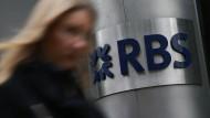 Eine Frau läuft an einem Logo der Royal Bank of Scotland vorbei.
