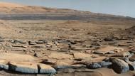 """Blick auf die """"Kimberly""""-Formation, aufgenommen 2015 vom Marsrover """"Curiosity"""" am Fuß des """"Mount Sharp"""". Die Gesteinsschichten im Vordergrund könnten in Folge der Ablagerung von Sand und Geröll entstanden sein."""