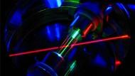 Auf dem Weg zur Atomkernuhr: Im Zentrum dieser Ionenfalle sitzen einzelne geladene Thorium-Atome.  Sie werden mit einem roten Laserstrahl bestrahlt und so lange gekühlt, bis ihre Bewegung eingefroren ist.