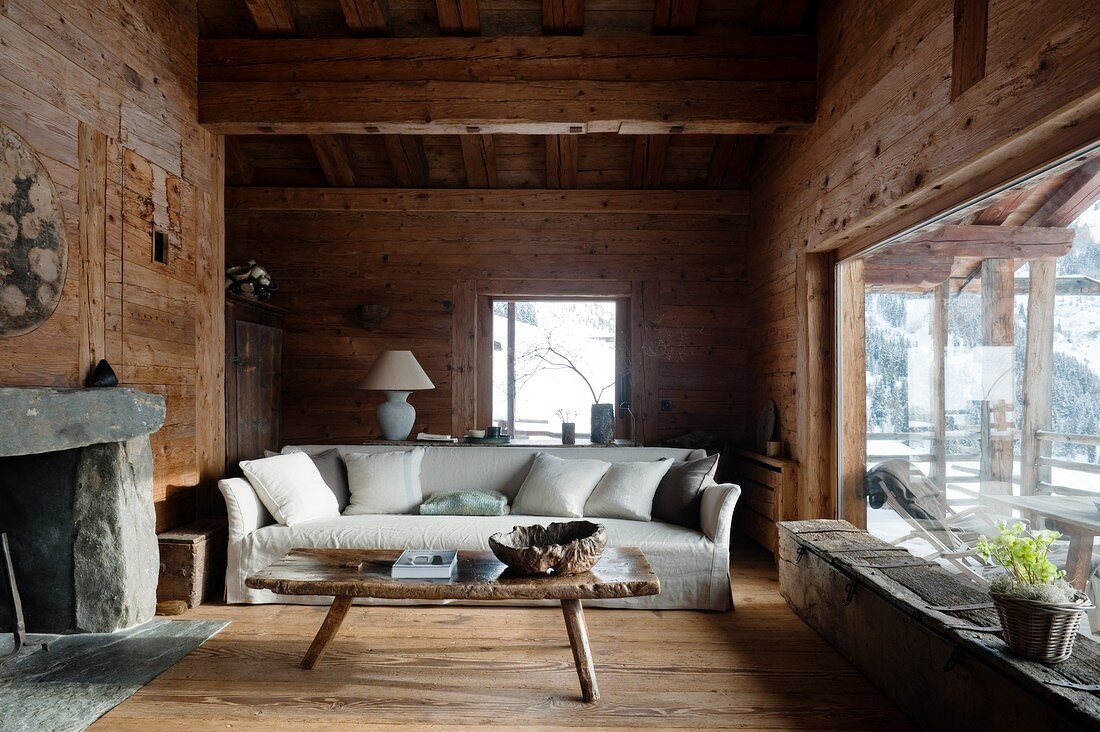 https www living4media com images 11286856 pale loose covered sofa with scatter cushions behind rustic wooden coffee table in living room of cabin with