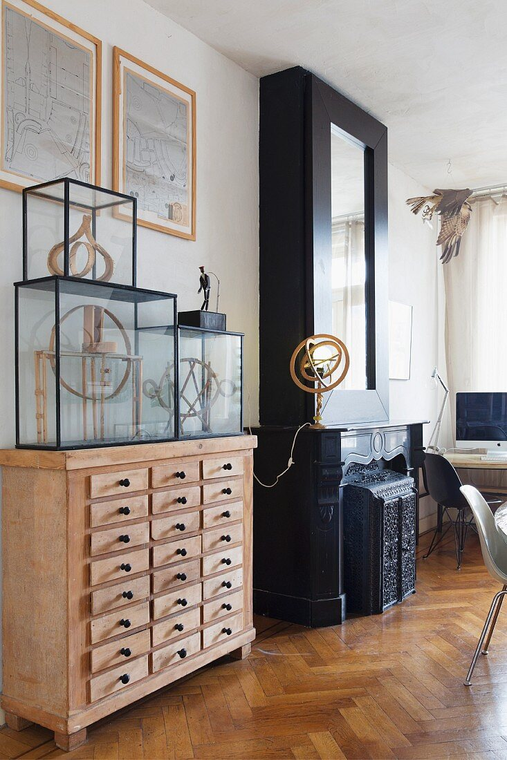 https www living4media com images 11315118 glass display cases on top of wooden apothecary cabinet next to fireplace with black surround and table lamp