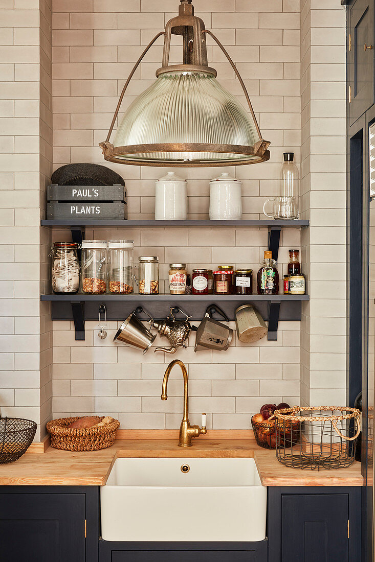 https www living4media com images 12560738 storage jars on shelves on tiled wall above kitchen counter with integrated sink and wooden worksurface