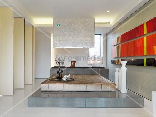 Modernes Schlafzimmer mit Bett auf Podest neben abstrakten Bildern an Wand  Bild kaufen