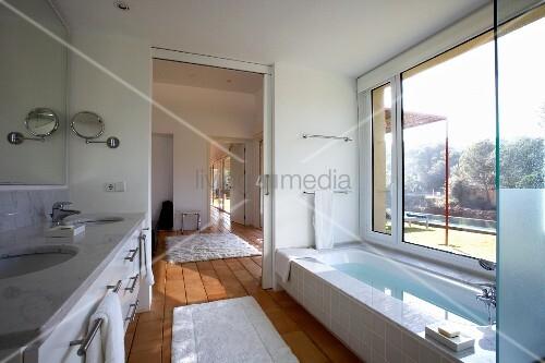Helles Badezimmer mit raumhohem Fenster Schiebetr und Terrakottafliesen  Bild kaufen
