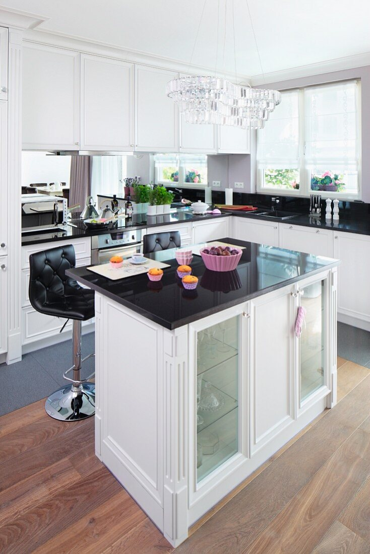 https www stockfood com images 11296876 an island counter in an elegant fitted kitchen with a crystal pendant light and lilac coloured baking moulds