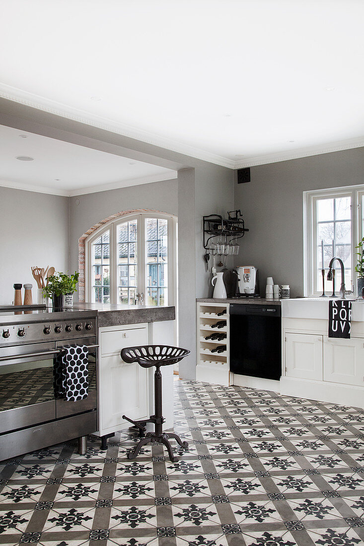 https www stockfood com images 13177118 a spacious country house kitchen in black white and grey with decorative floor tiles
