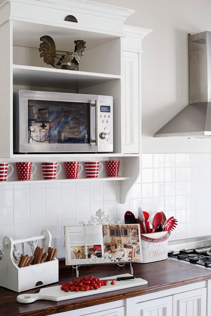 https www living4media com images 11137279 microwave in a white lacquer floating cabinet on a wall above a kitchen counter with utensils and cook book on