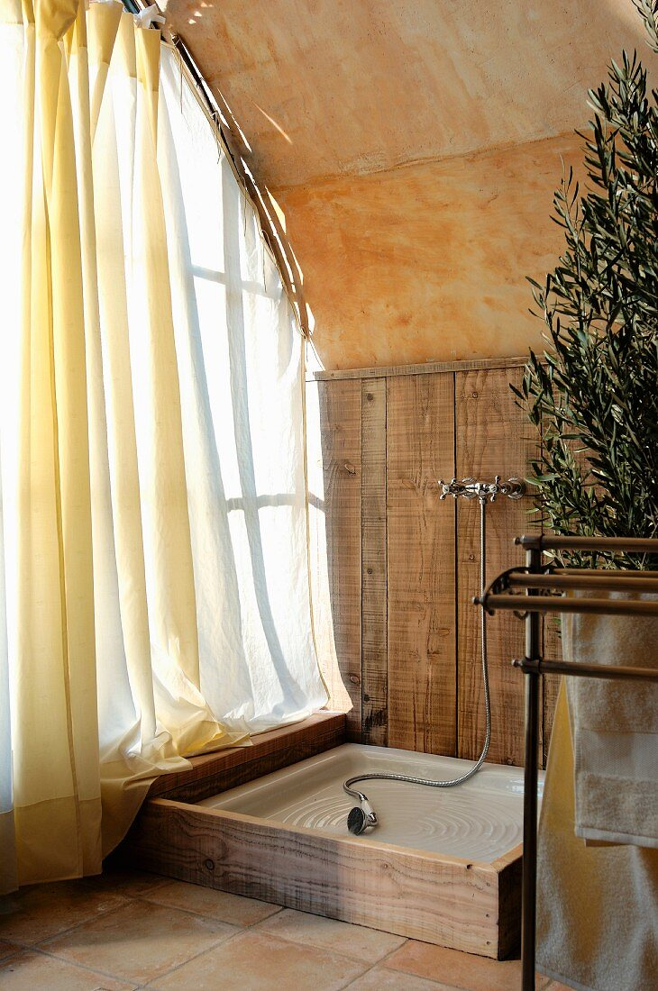 https www living4media com images 11173851 rustic shower area in corner next to window with airy curtain and barrel vaulted ceiling