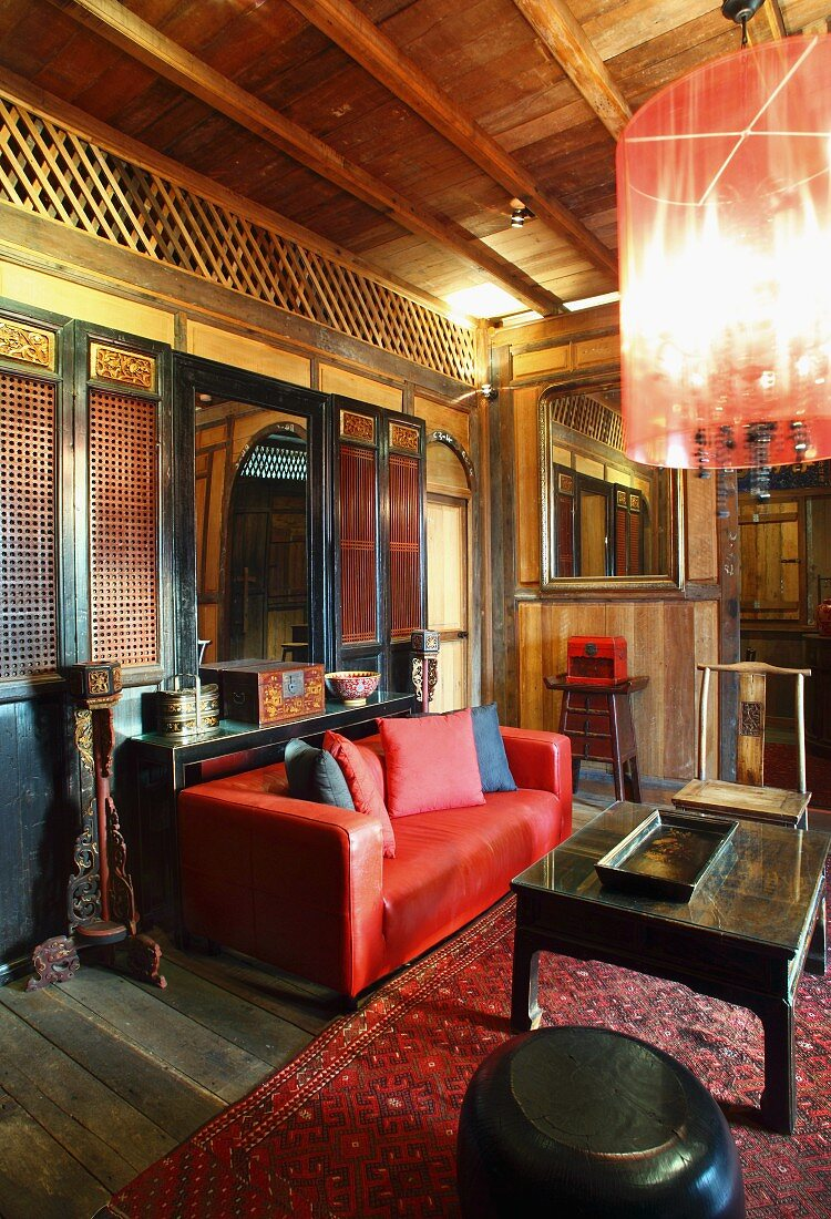 https www living4media com images 11081259 oriental lounge with wooden lattice walls red leather couch and black coffee table on rug