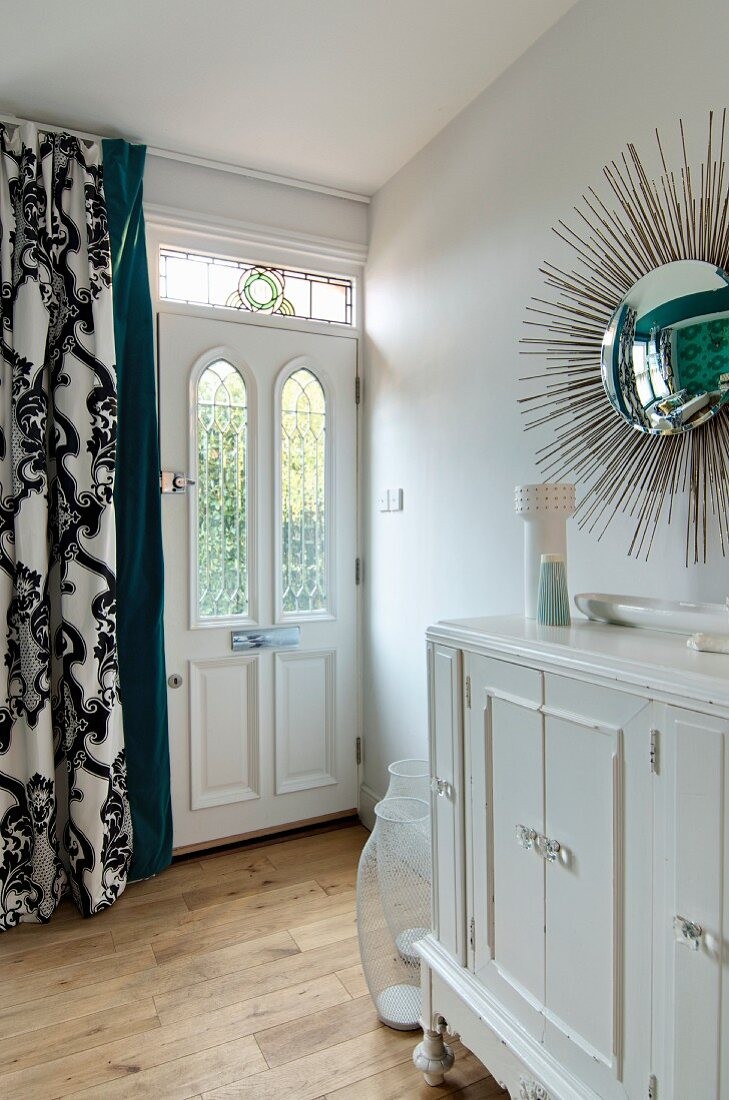 https www living4media com images 11313797 sunburst mirror above vintage cabinet front door with stained glass transom light and curtain with classic
