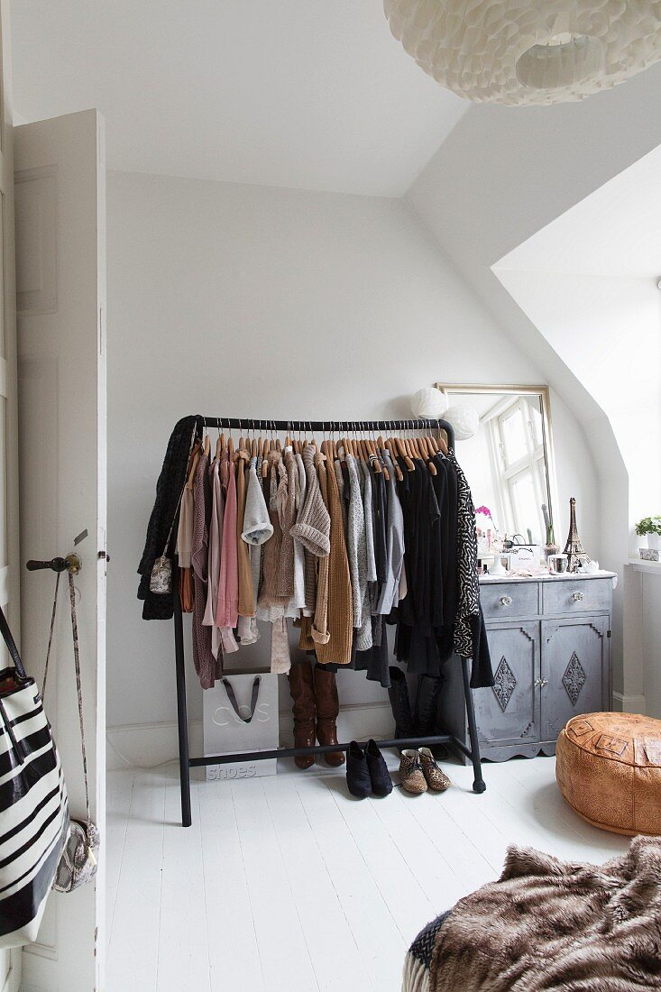 https www living4media com images 11325179 black clothes rack next to vintage cabinet in corner of bedroom with sloping ceiling
