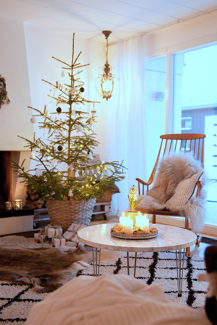 https www living4media com images 12344909 arrangement of candles on coffee table in front of christmas tree in cosy living room