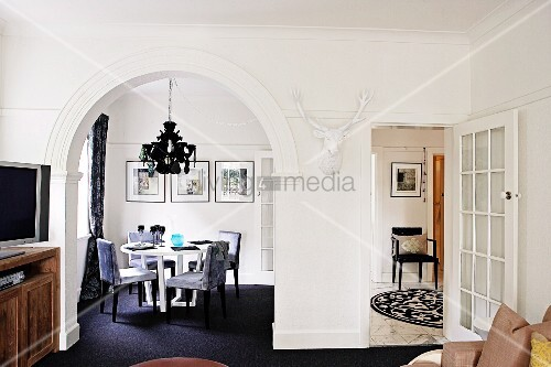 Living room with arched doorway leading to dining area