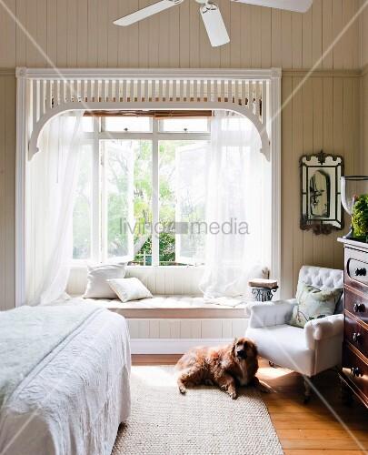 Hund vor einem Polstersessel im Schlafzimmer romantischer