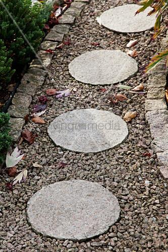 Runde Steinplatten auf gekiestem   Bild kaufen