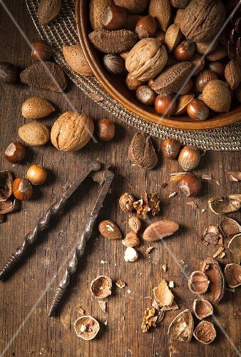 Festive bowl of mixed whole nuts in shells in a wooden bowl on a gold placemat