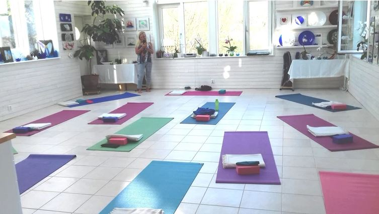 Bilden visar den stora ljusa ypgasal med en vackra yogamattor i lila, blå, rosa och grön. På varje yoga matta ligger en filt och en kudde.