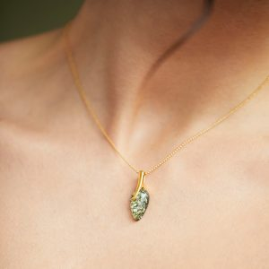 This classy and adorable necklace is created with sterling silver and gold plated with green genuine amber.