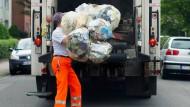 Ein Mitarbeiter der Abfallwirtschaft der Region Hannover wirft gelbe Säcke in einen Müllwagen.