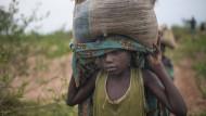 Im Kongo trägt ein Junge einen Sandsack zu einer Baustelle.