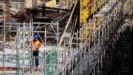 Ein Bauarbeiter steht auf einer Baustelle in Berlin.