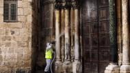 Desinfektionsmaßnahmen an der Eingangstür der Grabeskirche in Jerusalem.