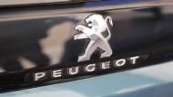 Das Logo des französischen Automobilherstellers Peugeot ist am Heck eines Autos befestigt.