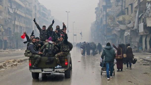 © AFP Anhänger des Assad-Regimes fahren durch Aleppo und feiern ihren Sieg.