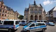 Mehrere Polizeifahrzeuge stehen nach einer Bombendrohung vor dem evakuierten Rathaus in Erfurt.