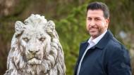 Ozan Iyibas, möglicher Bürgermeisterkandidat der CSU in Neufahrn, steht an einer Statue des Bayerischen Löwens. Einer Umfrage zufolge haben viele Bayern ein Problem mit Muslimen an der Stadtspitze.