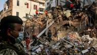 Mitglieder des chilenischen Rettungsteams und des libanesischen Zivilschutzes durchsuchen die Trümmer eines Gebäudes.