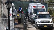 Patienten transportieren einen Patienten mit Atemschutzmaske in einen Krankenwagen.