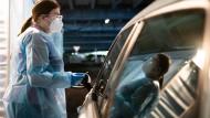 Eine Helferin testet Insassen eines Autos mit einem Schnelltest auf Corona.