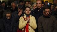Menschen beten gemeinsam beim Anblick des Brandes in der Pariser Kathedrale Notre-Dame.