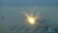 Heißer Druckauftrag: Wo der Laserstrahl das Metallpulver trifft, schweißt er es zu einer neuen Schicht des Werkstücks zusammen. Je nach verarbeitetem Metall wird dabei auf bis zu 3000 Grad Celsius eingeheizt.