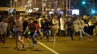 Minsk: Demonstranten laufen vor der Polizei weg.