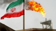 Eine iranische Flagge weht vor einer Ölförderanlage, wo Gas abgefackelt wird.