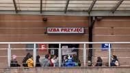 Menschen vor einem Krankenhaus in Posen, in dem zwei Ärzte mit dem Coronavirus infiziert sind.