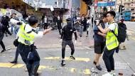 Ein Bild aus den Sozialen Medien zeigt einen Hongkonger Polizisten, als er mit seiner Waffe auf einen vermummten Demonstranten zielt.