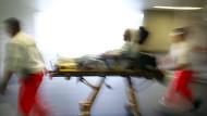 Rettungsassistenten liefern eine Notfallpatientin auf einer Trage in ein Krankenhaus ein.