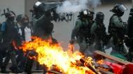 Ein Polizeibeamter geht mit Tränengas gegen Demonstranten vor.