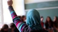 Eine Schülerin mit Kopftuch meldet sich in einem Oberhausener Gymnasium (Archivfoto).