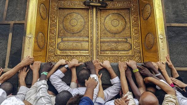 © dpa Sie waren nicht die ersten, die hier ihren Gott verehrten: gläubige Muslime vor der Goldenen Tür der Kaaba in Mekka
