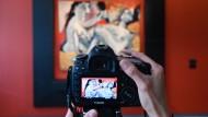 """Ein Besucher fotografiert das Picasso-Gemälde """"Les deux amis"""". An dem Bild """"Fillette au beret"""" des spanischen Malers kann er sich nun beteiligen."""