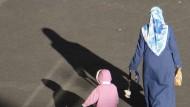 Eine Frau mit Kopftuch überquert mit ihrem Kind eine Straße in Berlin.
