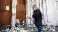 Erschüttert: Eine Frau legt am Freitag Blumen an der Kirche in Nizza nieder, wo ein Attentäter am Donnerstag drei Menschen tötete