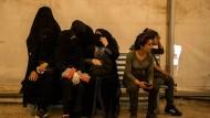 Verwandte von IS-Kämpfern sitzen bewacht von Kämpferinnen der Syrische Demokratischen Kräfte Anfang Juni im Flüchtlingslager Al Hol in der Provinz Hasakeh.