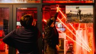 Eine Freundin von George Floyd wird durch eine Ausstellung am Tatort in Minneapolis geführt.