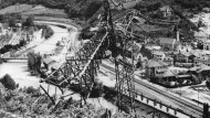 """Blick auf einen zerstörten Strommast in der Ortschaft Kardaun: In der sogenannten Feuernacht vom 11. auf den 12. Juni 1961 brachte der """"Befreiungsausschuss Südtirol"""" mit selbst hergestellten Bomben 37 Strommasten zu Fall."""